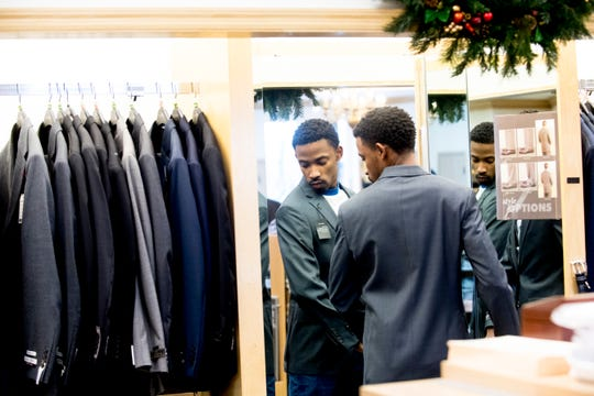 Trevon Covington tries on a suit jacket at Joseph Banks on Kingston Pike in Knoxville, Tennessee on Thursday, December 27, 2018. Marc Burnett, who is vice president for student affairs at Tennessee Tech, has been helping buy students their first suits for interviews.