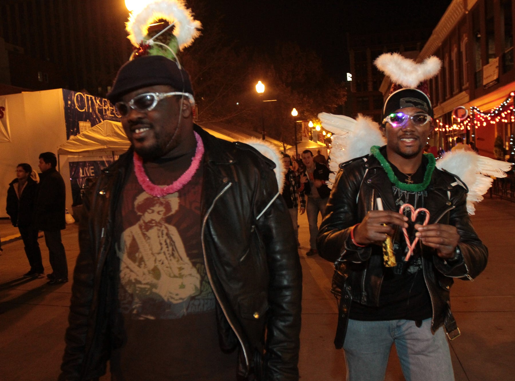 Marques Anderson and his brother Brent Anderson adorn wings and halos as they walk on the Market Square Mall during the New Year's Eve edition of First Night Knoxville on Friday, December 31, 2010.
