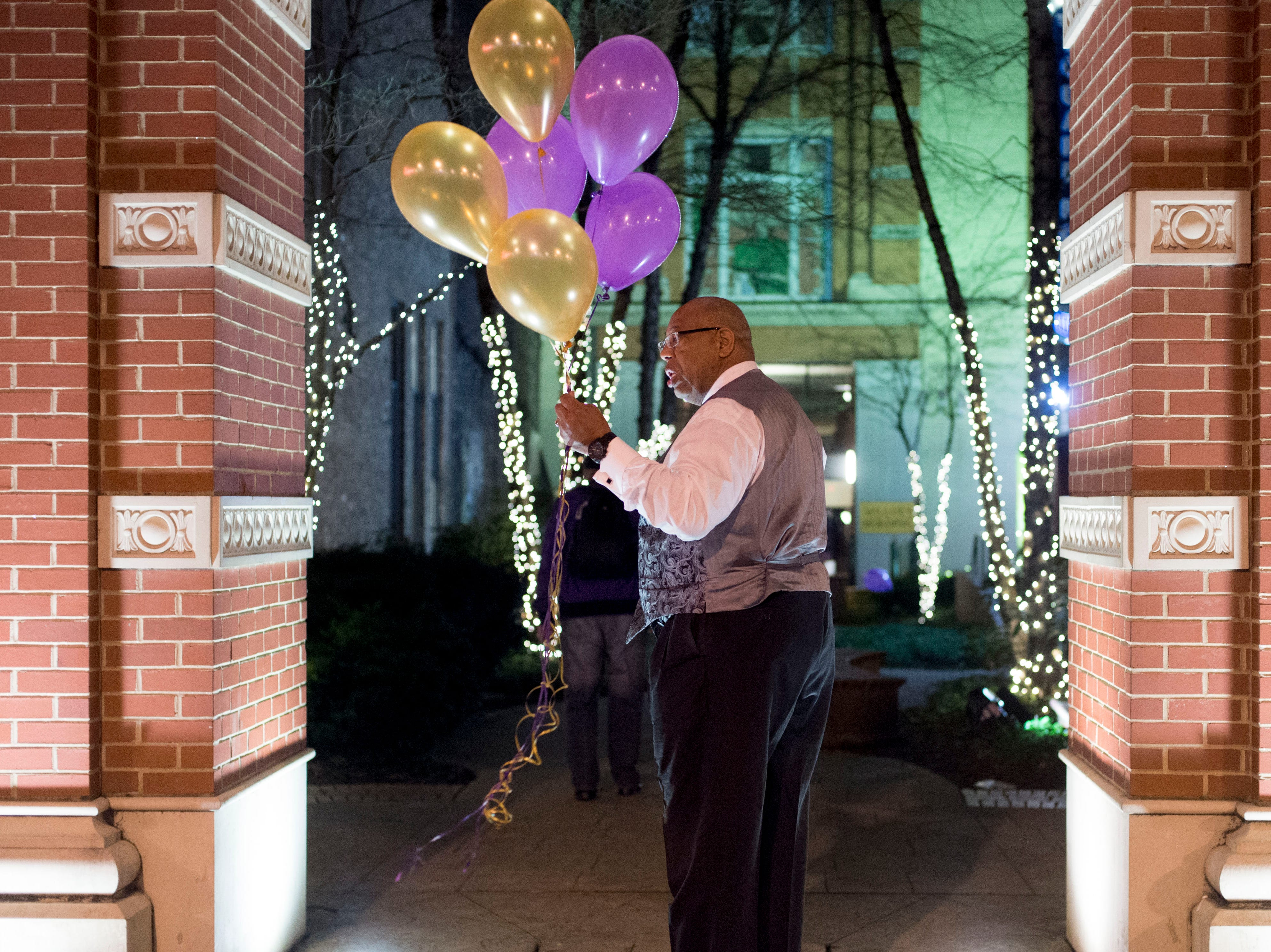 Bobby Leverett carries balloon and greets guest to a New Year's Even party for the Omega Psi Phi fraternity at Market Square, Thursday, December 31, 2015. The purple and gold balloons are the colors of his fraternity.