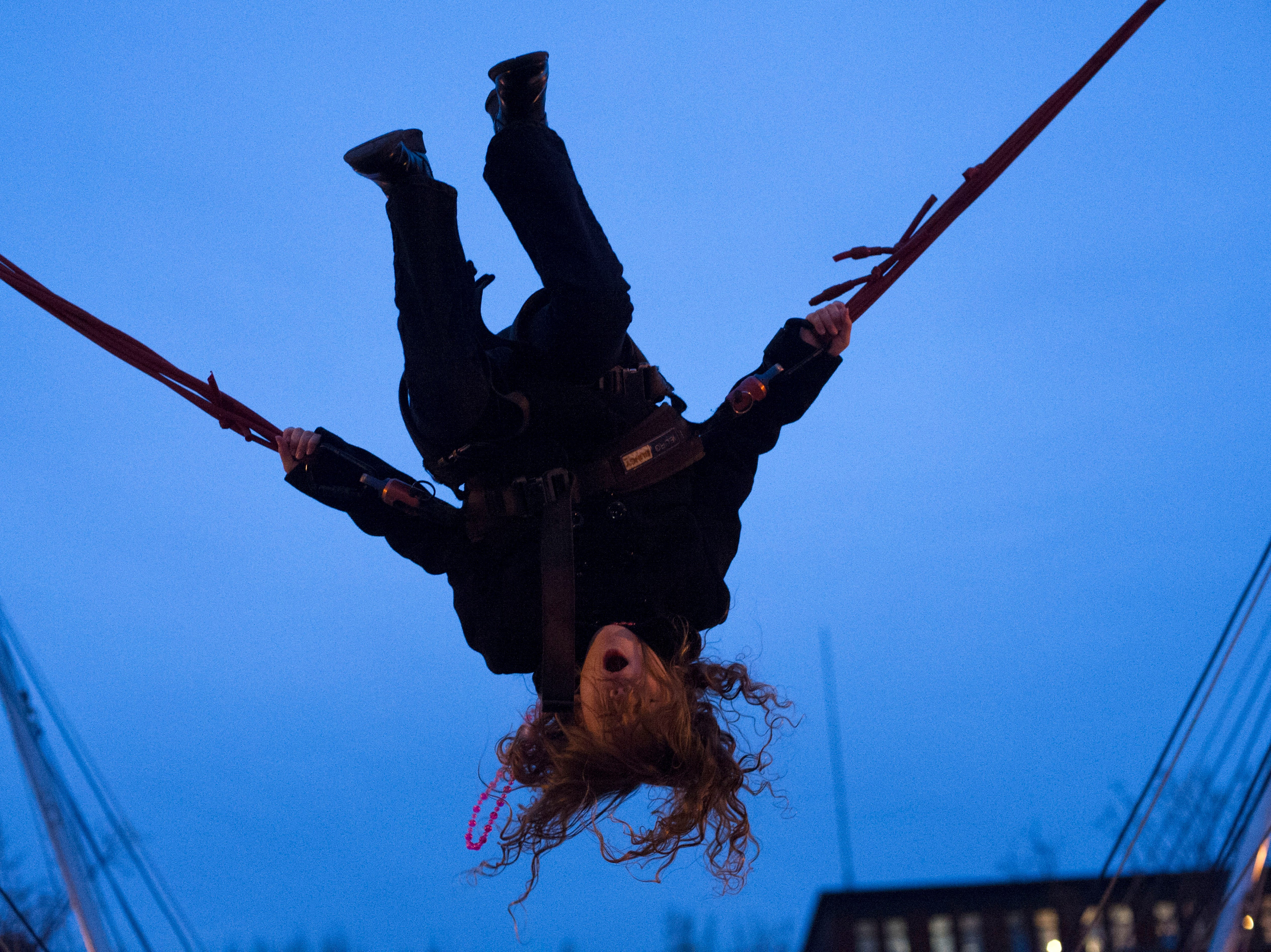 Keeley Kindt, 8, swings upside down on a bungee swing at Market Square during the City's New Year's Eve celebration on Monday, December 31, 2012.