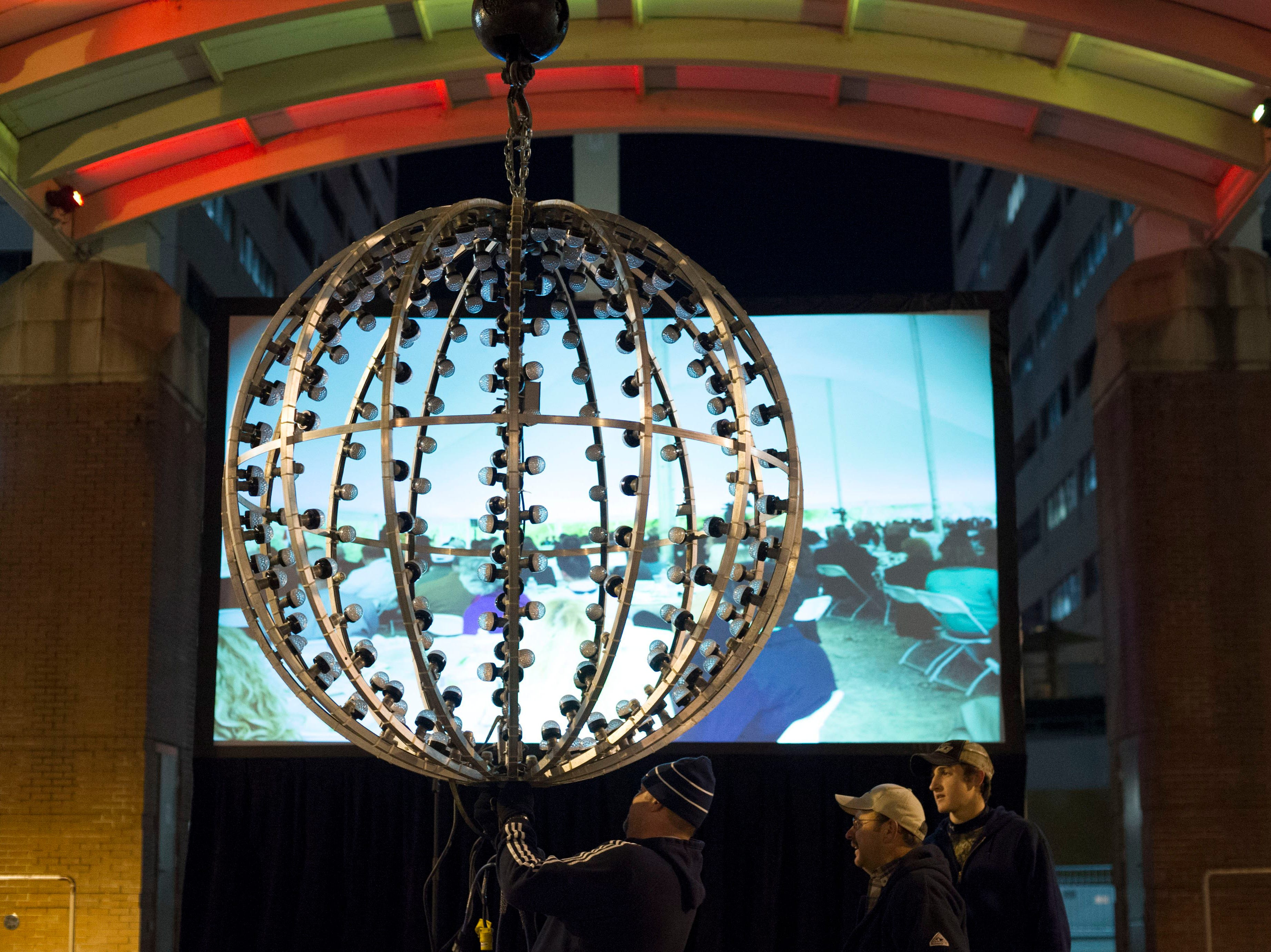 From left, Russell Taylor or Pyro Shows, Mark Brimer and his son Daniel Brimer of  Brimer Steel Erectors prepare the set up the ball for the New Year's Eve ball drop at Market Square on Tuesday, December 31, 2013.
