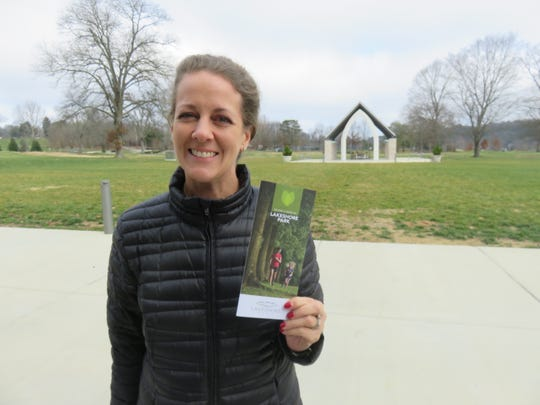 Lakeshore Park Conservancy director of development Cardin Bradley holds up a brochure discussing the name change of the nonprofit organization overseeing Lakeshore Park.