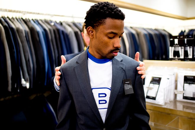 Trevon Covington tries on a suit with salesman Todd Rowland at Joseph Banks on Kingston Pike in Knoxville, Tennessee on Thursday, December 27, 2018. Marc Burnett, who is vice president for student affairs at Tennessee Tech, has been helping buy students their first suits for interviews.