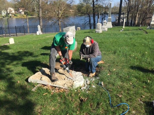 Dave Pettigrove and Jim Vichich, president of the Brighton Area Historical Society, work on a headstone at the Old Village Cemetery adjacent to the Mill Pond. Restoration of 148 grave markers has been ongoing for the past six summers and will continue in 2019.