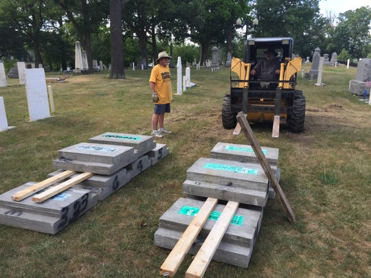 Joe Collins (standing) and Dave Fuller at work in the Old Village Cemetery this summer, where headstone restoration has been ongoing for the past six years.