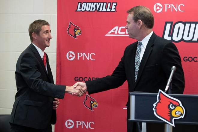UofL soccer assistant coach John Michael Hayden, left, shakes hands with athletic director Vince Tyra after he was named the new head coach Thursday. Dec. 27, 2018