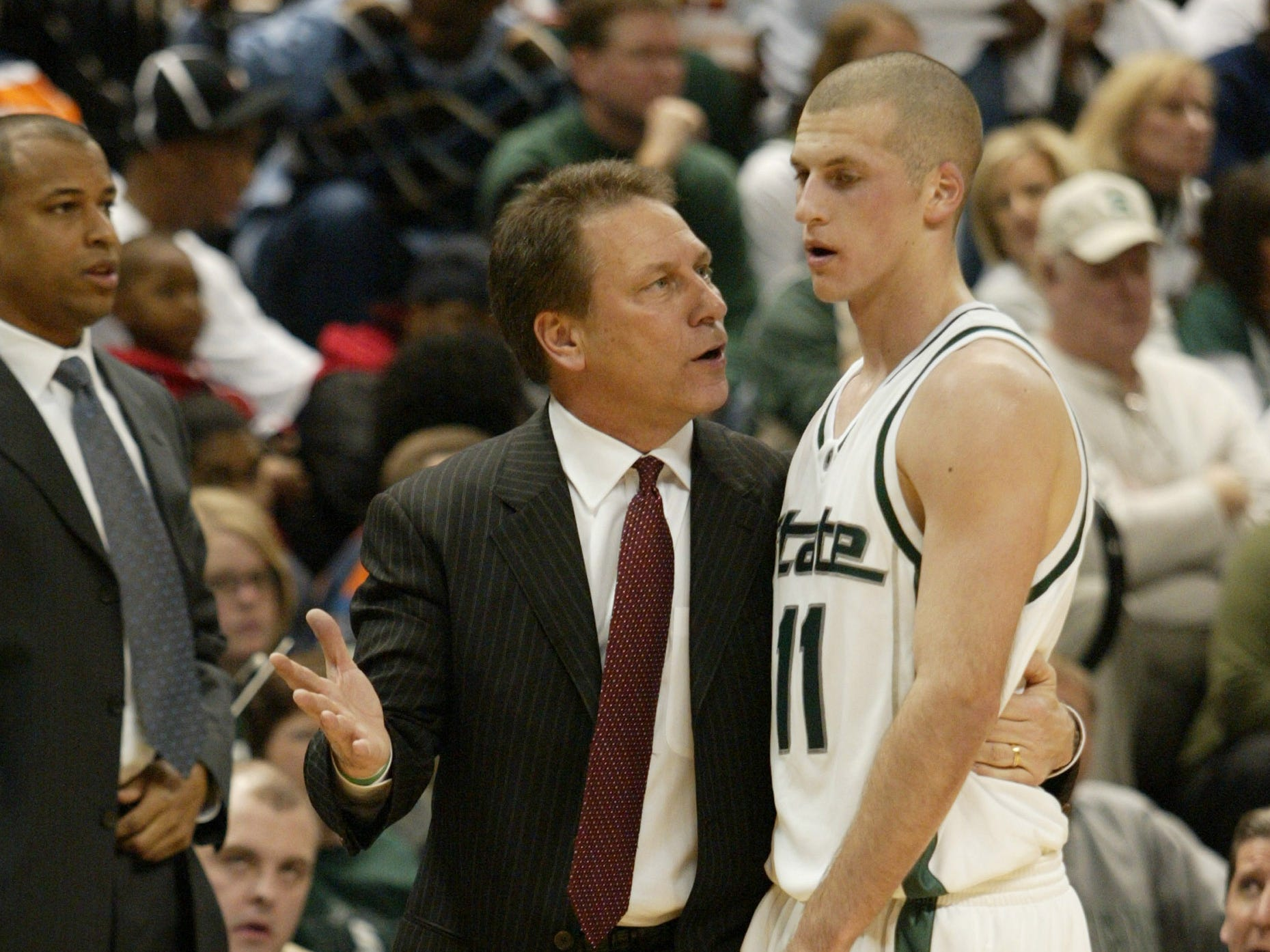 Michigan State head coach Tom Izzo speaks Drew Neitzel (11) as he comes off the court in the Spartans'  90-71 victory over Michigan on Feb. 18, 2006, in East Lansing. Assistant coach Mark Montgomery is in the background.