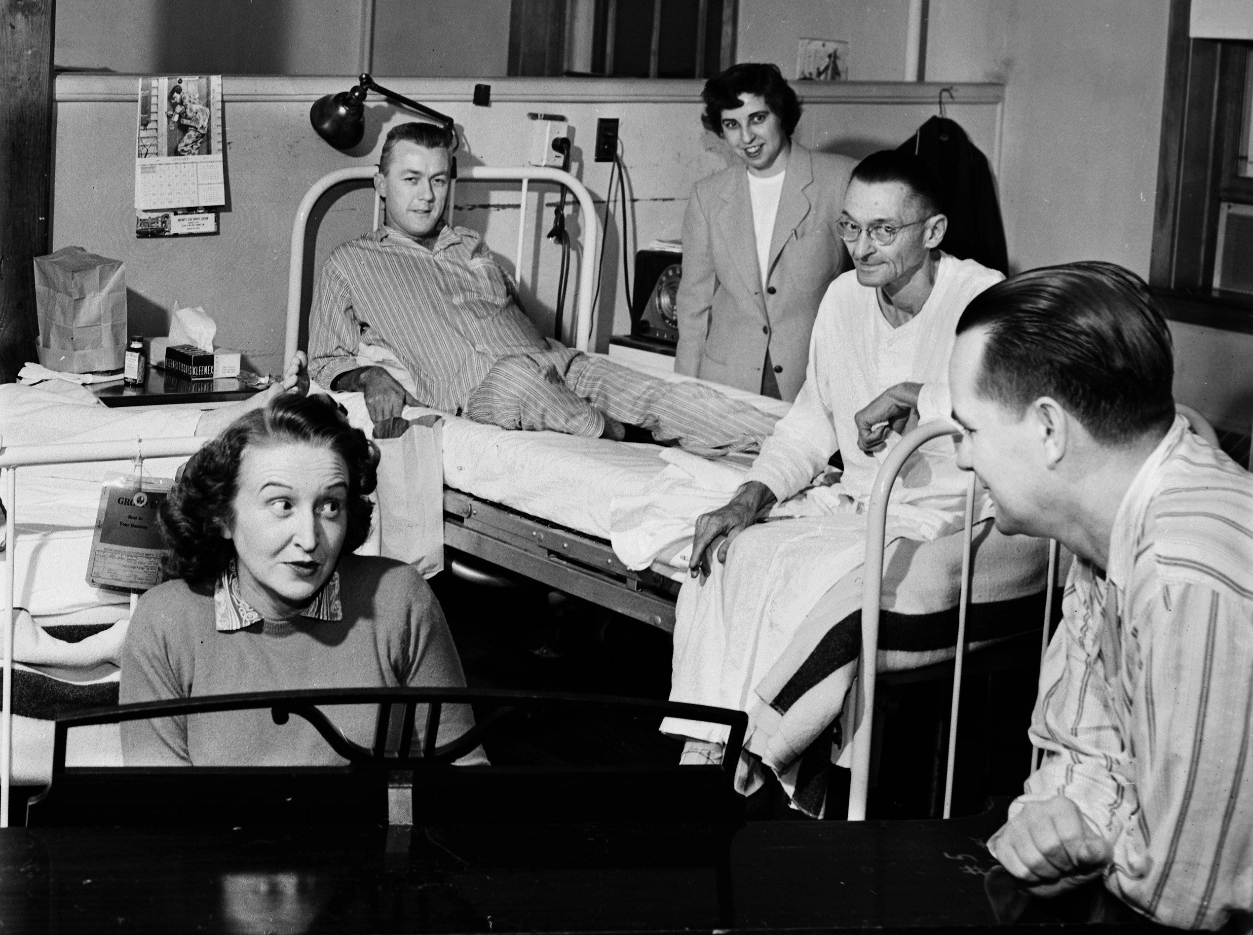 Mrs. Ernestine Hall (Left) of 1351 Linden, and the portable piano behind which she is seated, have become familiar and well-loved fixtures at Kennedy Veterans Hospital where Mrs. Hall has entertained patients with her wide repertoire of songs for 10 years.  Enjoying one of her musical interludes in a hospital ward in January 1952 are (From Second Left) Woodrow McClure  of Paragould, Ark., World War II Army veteran; Miss Genevieve Antonelli of 1328 South Barksdale, Miss Hall's supervisor; P.B. Wonsey of Wichita, Kan., World War I Army veteran and Alvin E. Branch, Air Force veteran from Union City, Tenn.