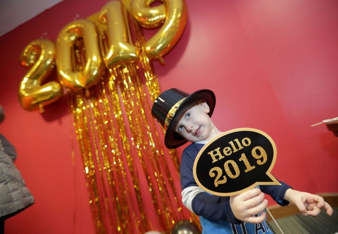 Natan Rogovskiy, 2, has his photo taken in the makeshift photo booth by his mother, Nadiia Rogovskiy (not pictured), during the Happy Noon-Year party at North Shore Library in Glendale Thursday to ring in the new year early. Children and adults celebrated with noisemakers, hats, a photo booth, treats and a countdown at noon.