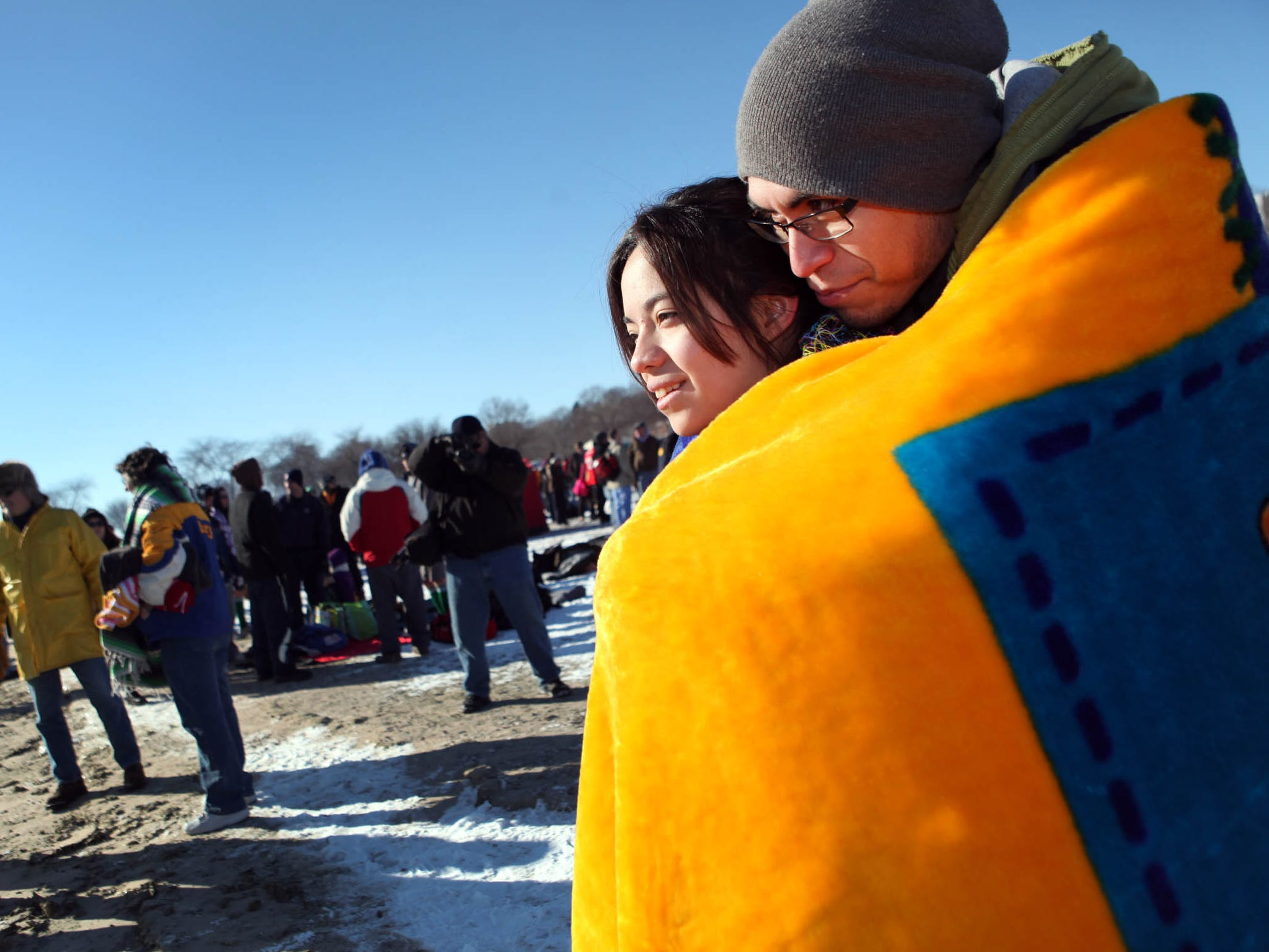 Isis Lozano of Milwaukee prepares for her first time participating in the Polar Bear Plunge at Milwaukee's Bradford Beach on Jan. 1, 2013, staying warm with the help of her boyfriend, Jesus Rodriguez of West Allis.