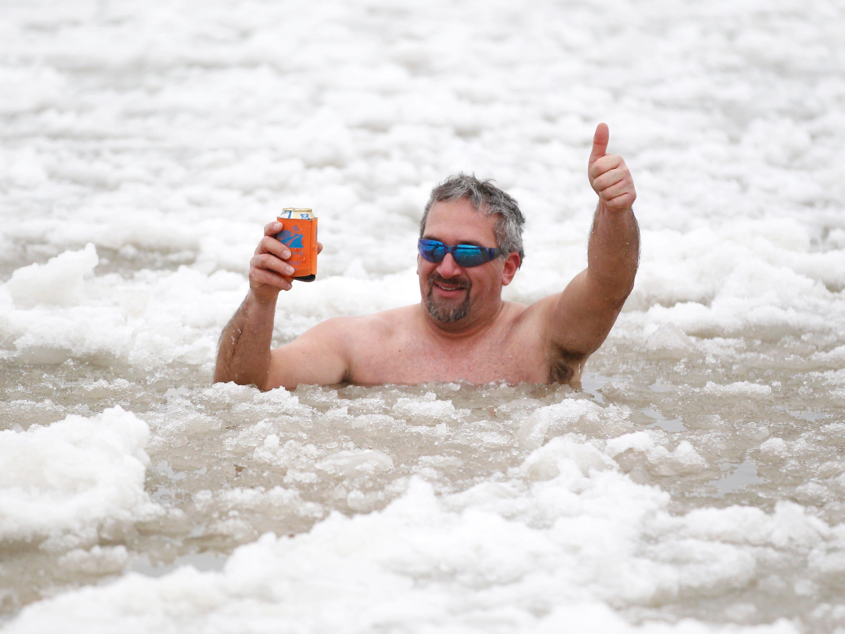 Jeff Kopp of Waukesha gives a thumbs up while lounging with his adult beverage surrounded by ice-filled water at Bradford Beach, after the annual Polar Bear Plunge on Jan. 1, 2014.