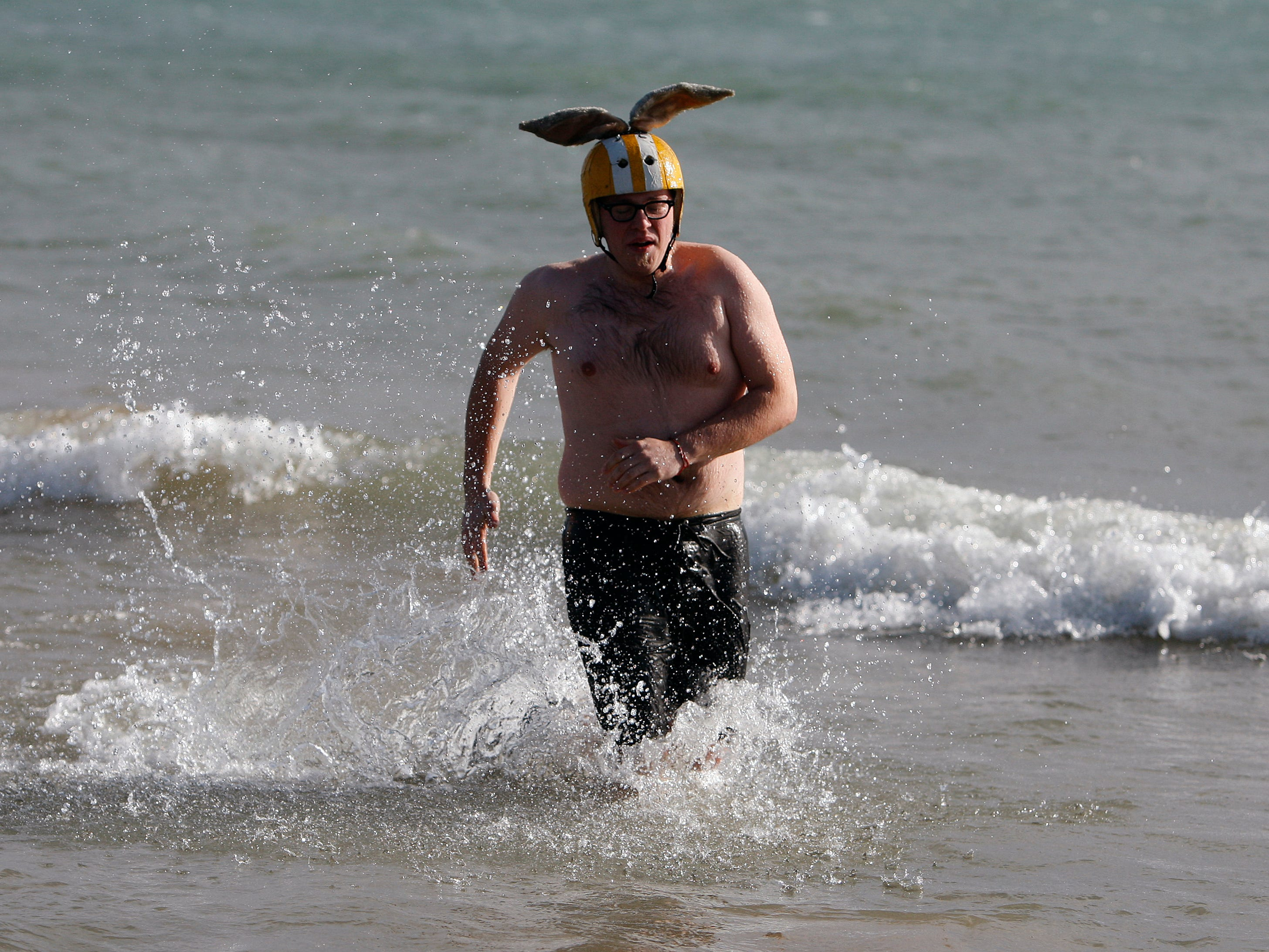 A man tries to take wing during the Polar Bear Plunge at Bradford Beach on Jan. 1, 2011.