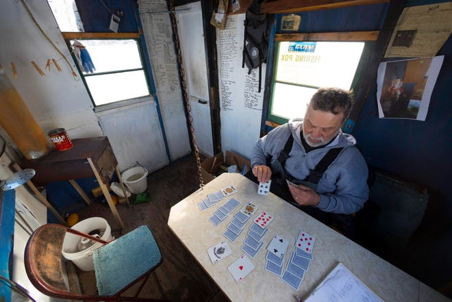 Dan Brokiewicz plays solitaire in his ice fishing shack while monitoring his tip-ups on Dec. 24 on Shawano Lake in Cecil. Tip-ups are fishing lines placed in an ice hole with a mechanical strike indicator that raises a flag when a fish is on the line.