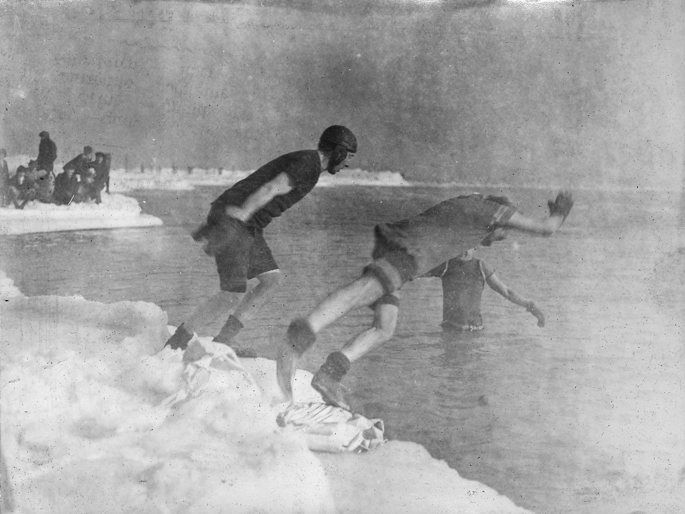 A pair of the city's earliest known polar plungers — Frank Sutter (left) and Jim Brazell — jump from the icy shore to join Gustav Marx in Lake Michigan in a photo dated Dec. 31, 1916.