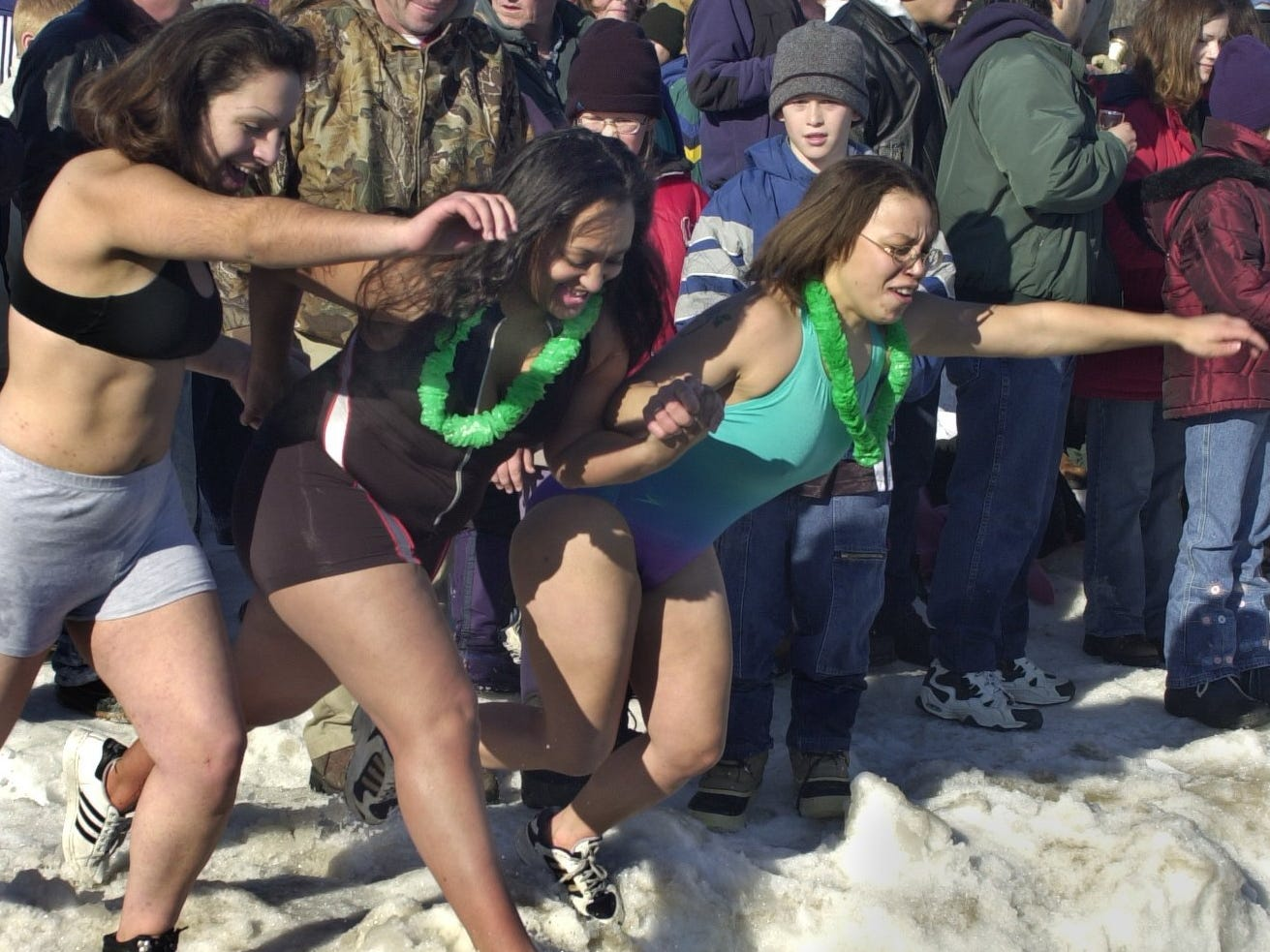 Three women leap into Lake Michigan off a snowbank on Bradford Beach during the Polar Bear Plunge on Jan. 1, 2001.