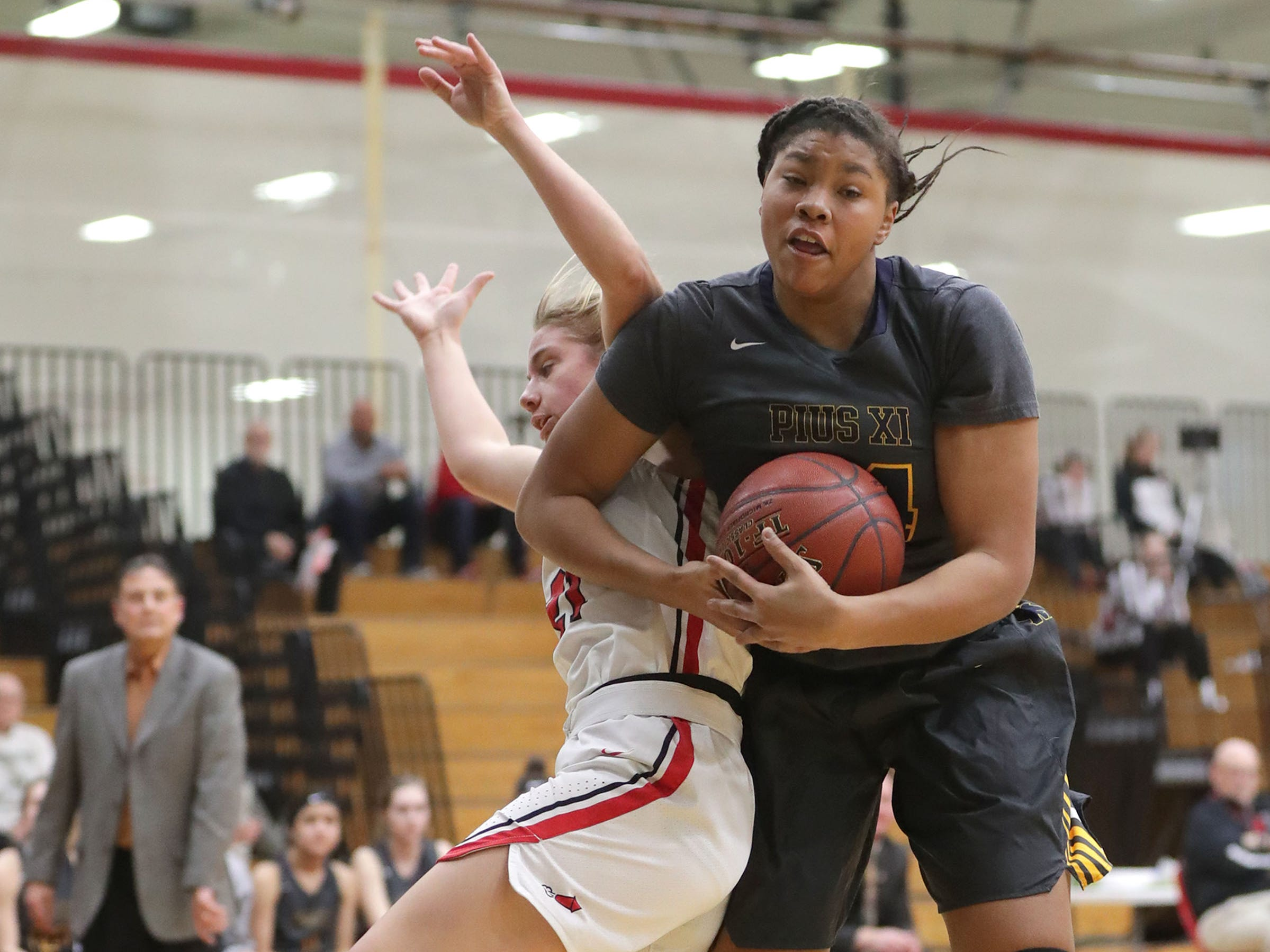 Pius XI's Mya Moore rips a rebound away from South Milwaukee's Paige Lathrop on Thursday, Dec. 27, 2018, during the Holiday Shootout at Waukesha South.