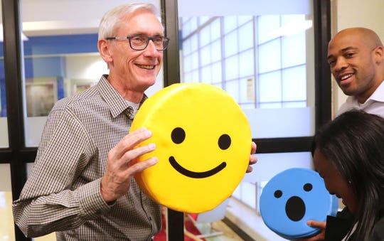 Gov.-elect Tony Evers jokingly holds a smiley emoji pillow to reflect how he's feeling after winning the election as he and Lt. Gov.-elect Mandela Barnes visit the Boys & Girls Club of Dane County in Madison Nov. 7, the morning after he was elected governor.