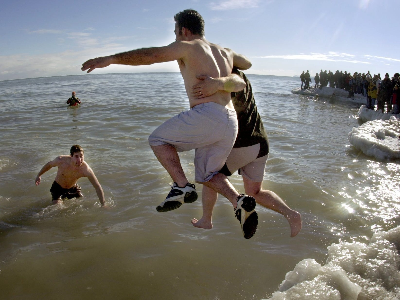 A couple take the leap into Lake Michigan from the ice-covered bank of Bradford Beach during the Polar Bear Plunge on Jan. 1, 2001.