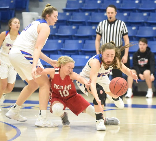 Highland's Cheyenne Yates and Paragould's Blythe Benefield dive for a loose ball Thursday.