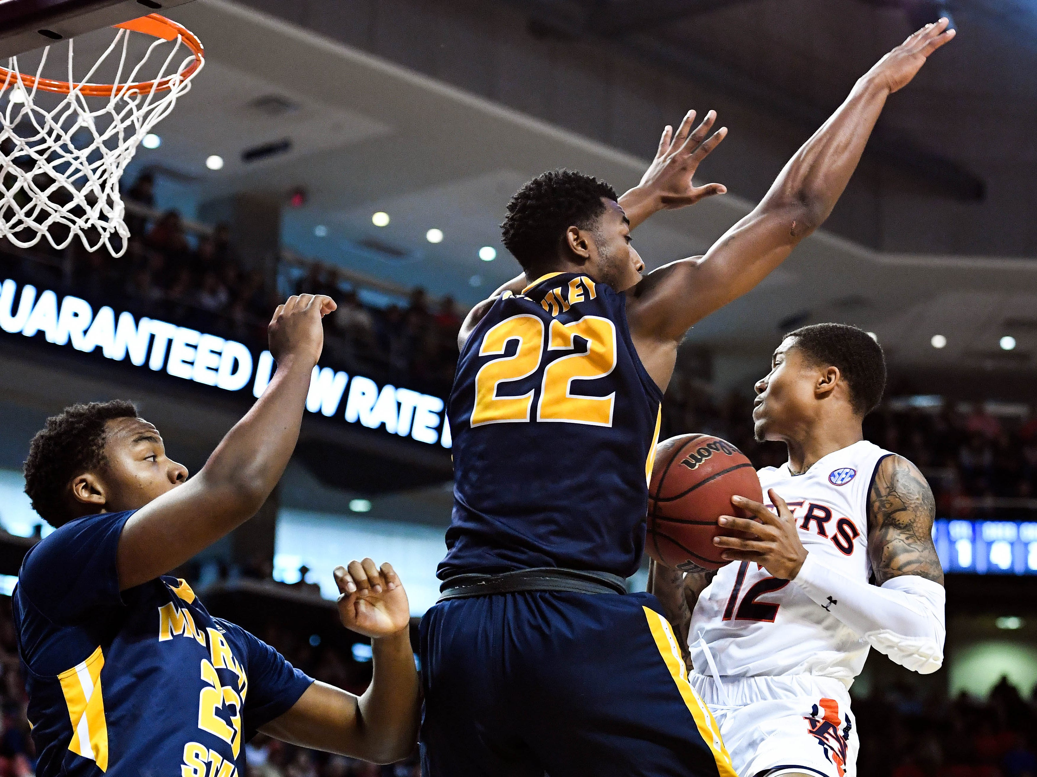 Dec 22, 2018; Auburn, AL, USA; Auburn Tigers guard J'Von McCormick (12) is defended at the net by Murray State Racers guard Brion Whitley (22) and forward KJ Williams (23) during the first half at Auburn Arena. Mandatory Credit: Shanna Lockwood-USA TODAY Sports