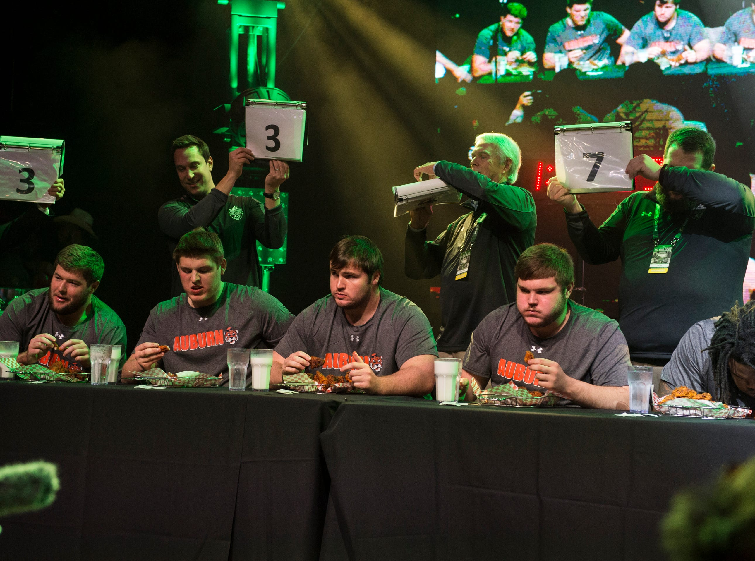 Auburn players compete in a hot chicken eating competition at Wild Horse Saloon in Nashville, Ten., on Wednesday, Dec. 26, 2018. Auburn takes on Purdue in the Music City Bowl Friday.