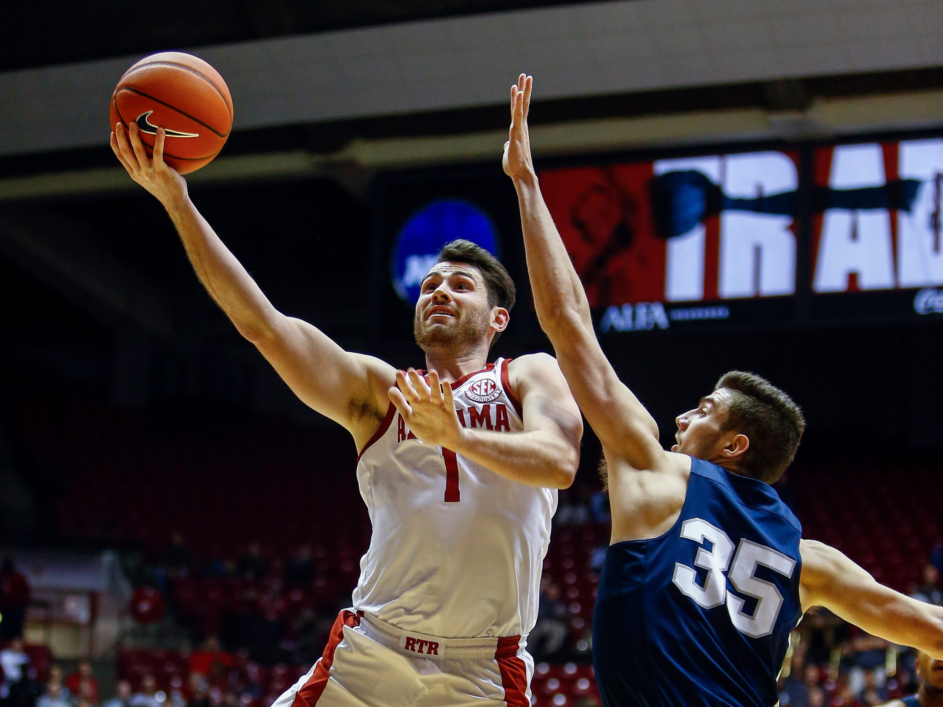 Dec 21, 2018; Tuscaloosa, AL, USA; Alabama Crimson Tide guard Riley Norris (1) shoots the ball past Penn State Nittany Lions forward Trent Buttrick (35) during the second half of an NCAA college basketball game at Coleman Coliseum. Mandatory Credit: Butch Dill-USA TODAY Sports