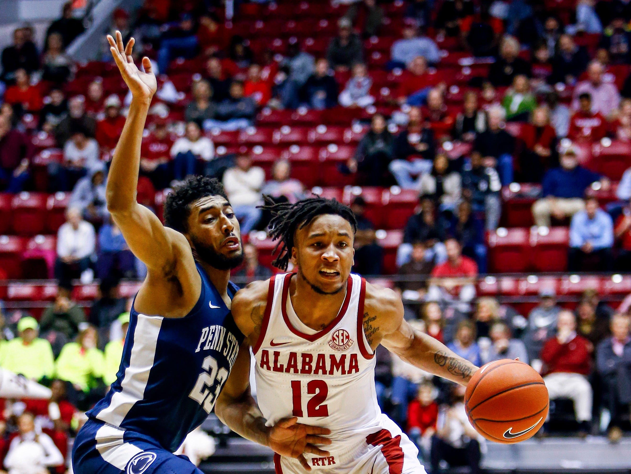 Dec 21, 2018; Tuscaloosa, AL, USA; Alabama Crimson Tide guard Dazon Ingram (12) dribbles the ball past Penn State Nittany Lions guard Josh Reaves (23) during the second half of an at Coleman Coliseum. Mandatory Credit: Butch Dill-USA TODAY Sports