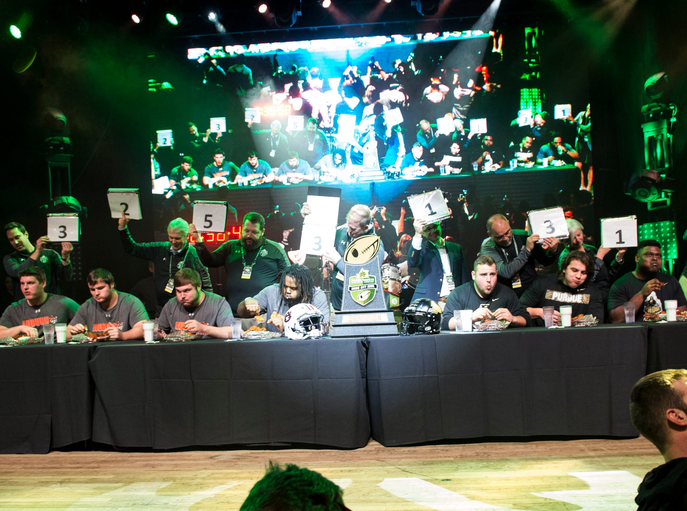 Auburn and Purdue players compete in a hot chicken eating competition at Wild Horse Saloon in Nashville, Ten., on Wednesday, Dec. 26, 2018. Auburn takes on Purdue in the Music City Bowl Friday.