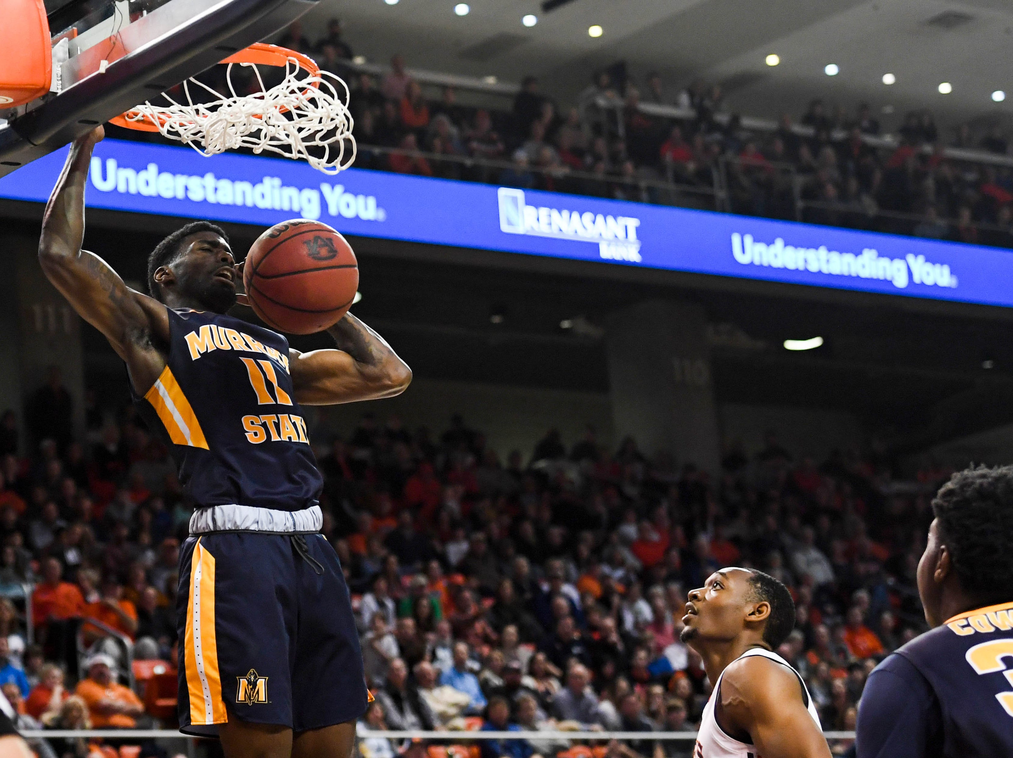 Dec 22, 2018; Auburn, AL, USA; Murray State Racers guard Shaq Buchanan (11) dunks as Auburn Tigers center Austin Wiley (50) looks on alongside Murray State Racers forward Darnell Cowart (32) during the first half at Auburn Arena. Mandatory Credit: Shanna Lockwood-USA TODAY Sports