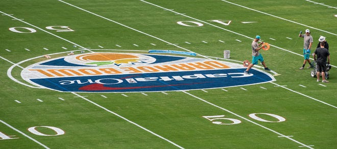 Workers paint the field at the Hard Rock Stadium in Miami Gardens, Fla., on Wednesday December 26, 2018.