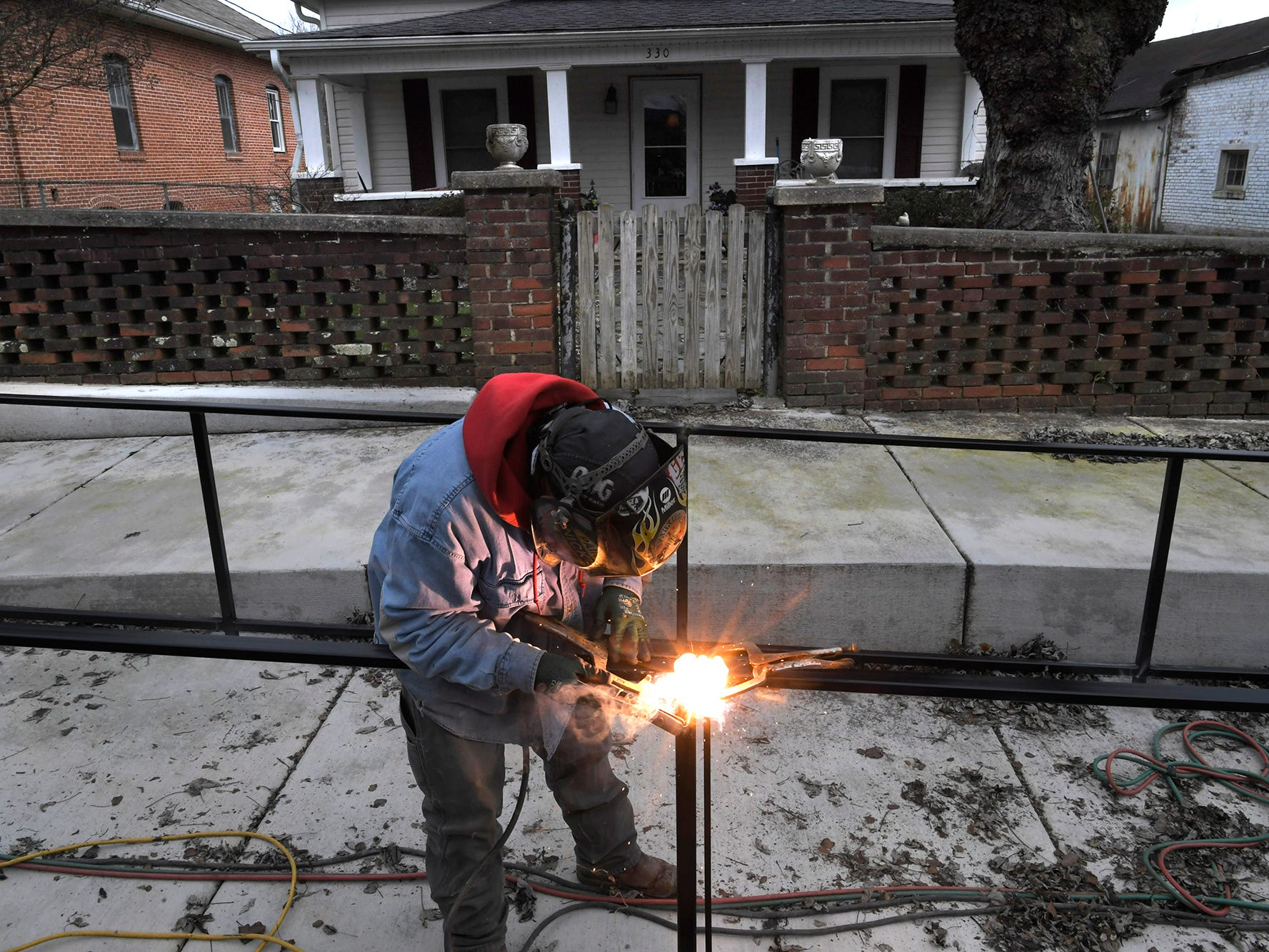 Carlos Peinado welds sidewalk railings in downtown Ducktown on Dec. 4, 2018. The town recieved a grant to upgrade its to sidewalks, landscaping, signage and pedestrian lighting.
