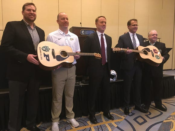 Purdue coach Jeff Brohm, second from left, and Auburn coach Gus Malzahn, second from left, were presented with guitars at a joint press conference for the Music City Bowl Thursday. Music City Bowl co-chairman Brad Lampley, far right, is also pictured along with Franklin American Mortgage representative Scott Tansil, center, and co-chairman Richard Pinson, far right.