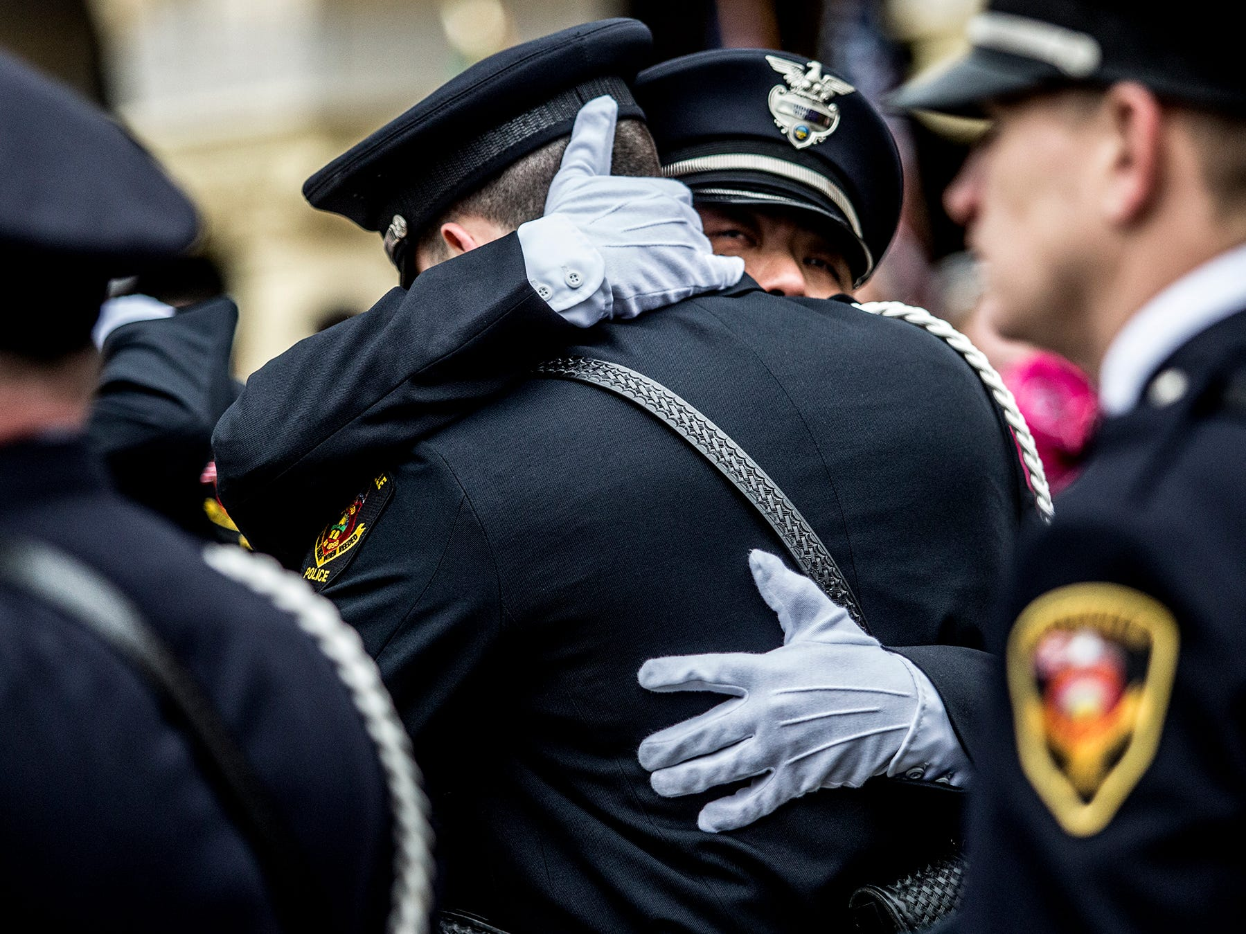 Westerville police officers console each other after attending services for fallen comrades, Eric Joering and Anthony Morelli. Last weekend Westerville officers Joering and Morelli were killed in the line of duty while responding to s domestic violence call.