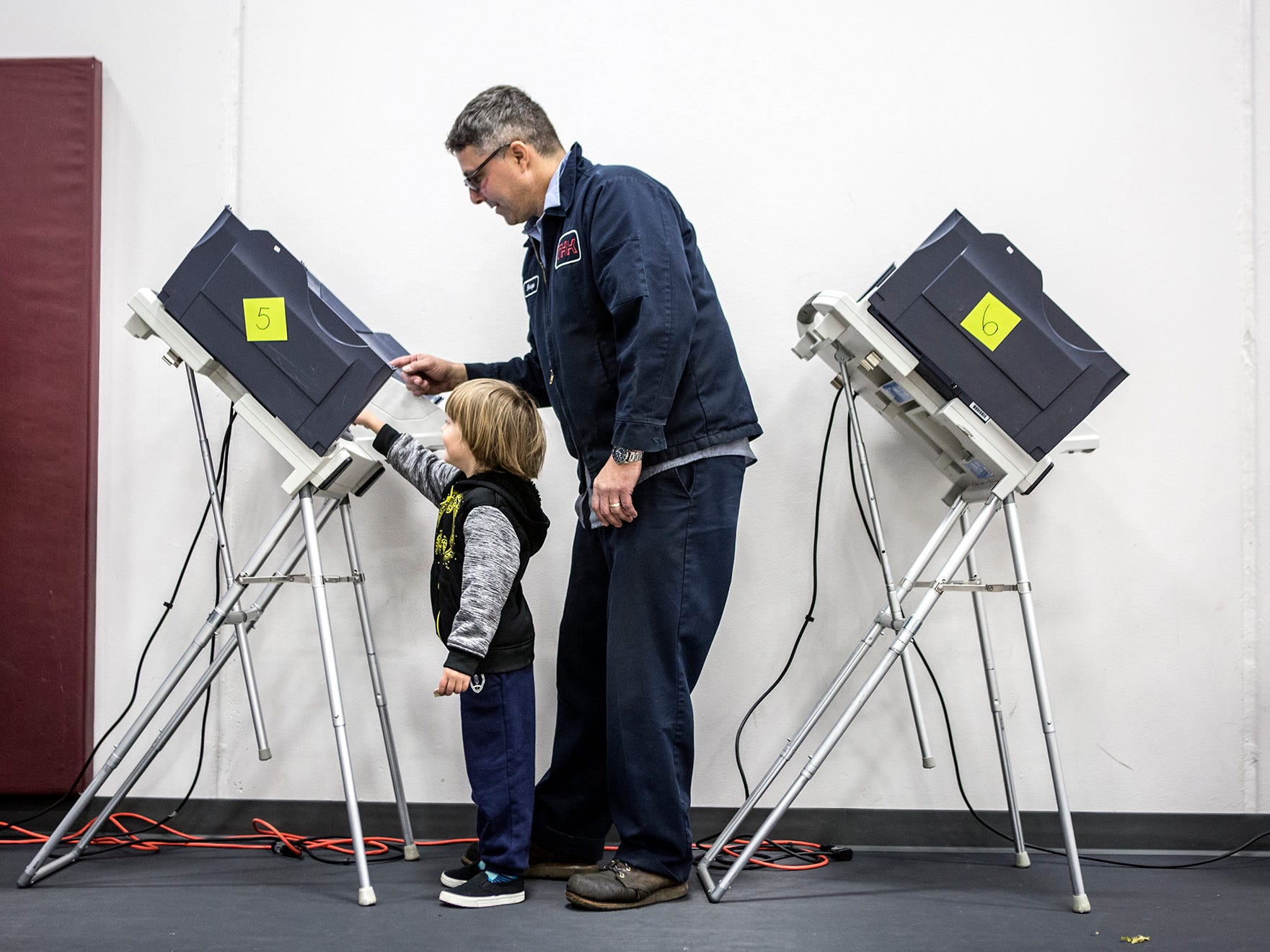 Daniel Hoops, 4, helps his dad, Bryan vote Tuesday at the Licking County YMCA for the 2018 midterm elections.