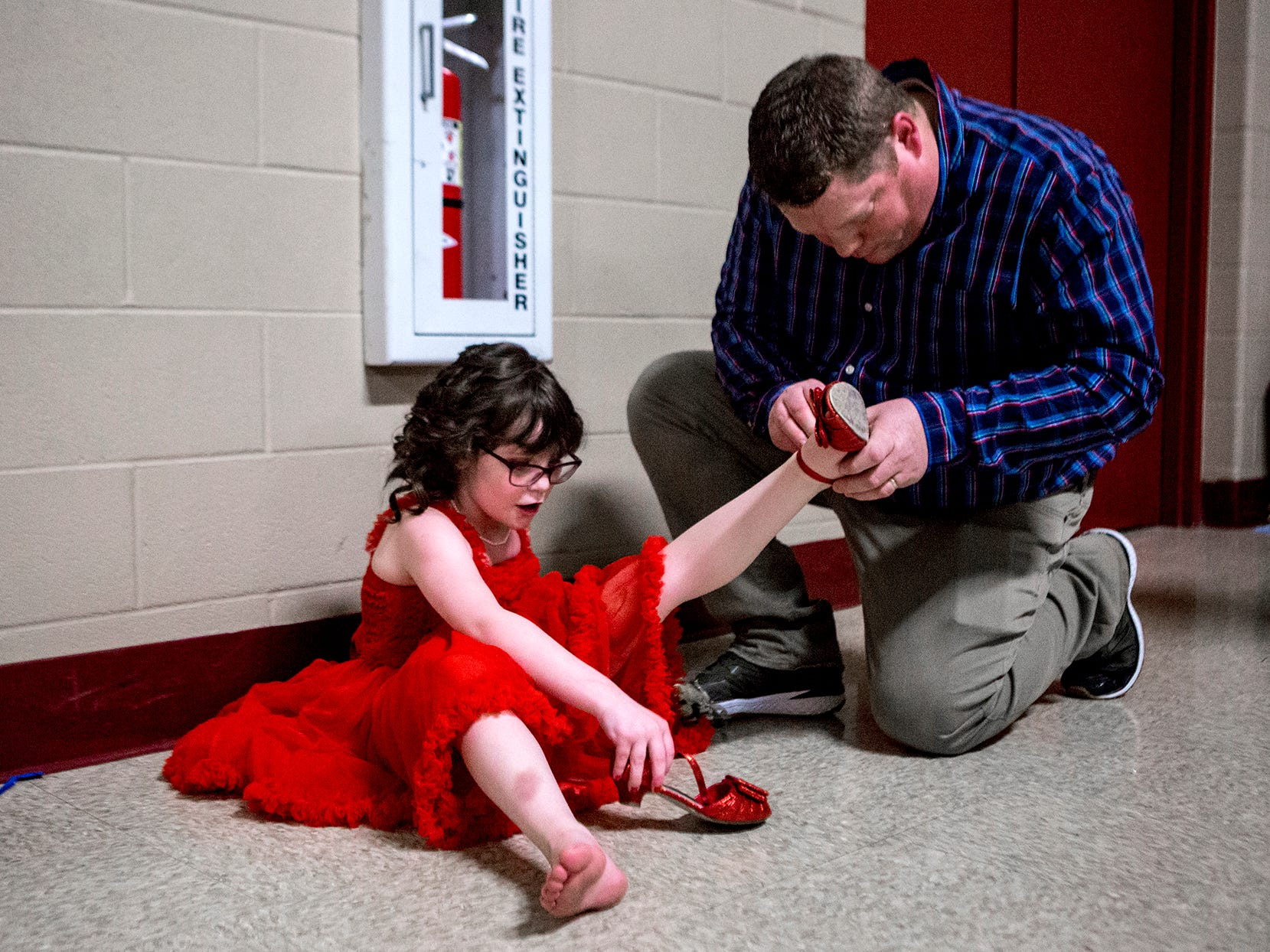 Brian McGuire puts the shoes back on his daughter, Brigid's feet halfway through the annual daddy daughter dance.