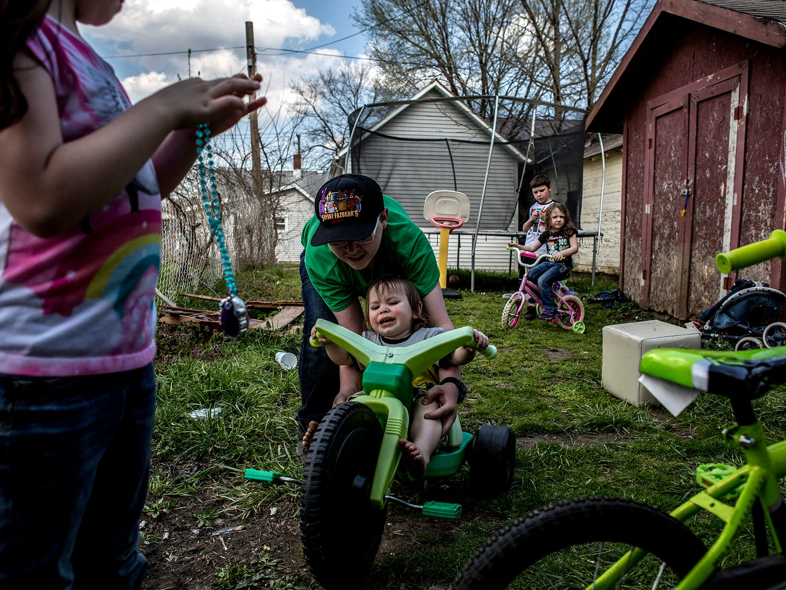 The Crawford children play in their backyard on a spring day as a storm begins to roll in.