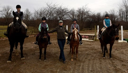 Kathy Lloyd, of Grenoble Stables in Granville, with riding students Kamryn Kirkham, Ava Roof, Emma Meier, and Poppy Herro after a lesson.