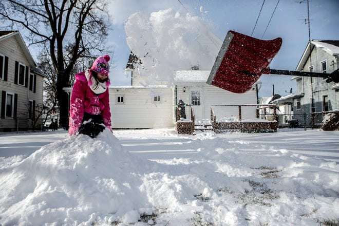 Becca, 7, prepares herself as a shovel full of snow her dad, Dustin, launched at her as they played in the snow in their backyard in December in Newark.