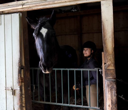 Riding student Kamryn Kirkham burshes horse, Macey, after a riding lesson at Grenoble Stables in Granville.