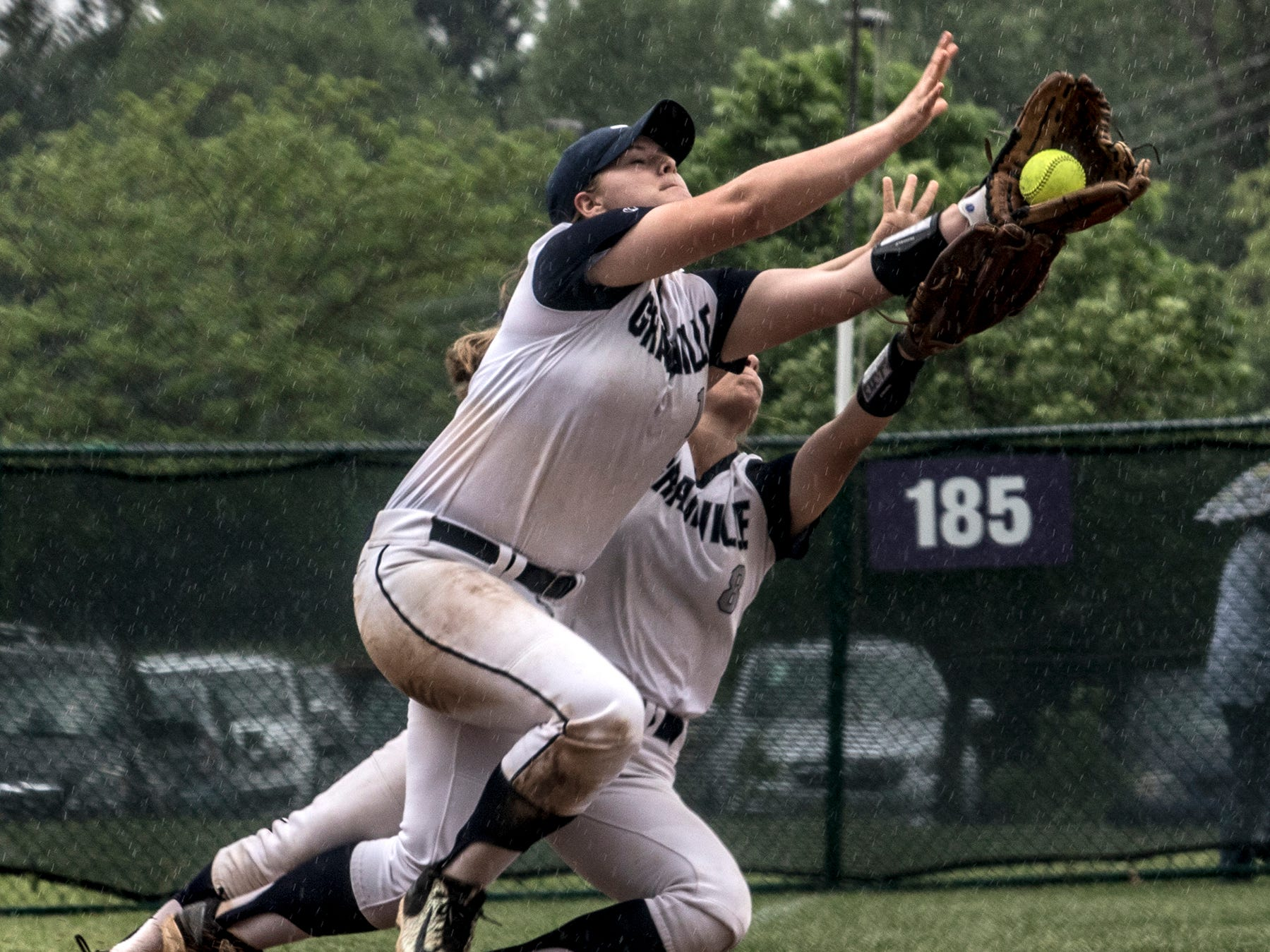 Reghan Benshoter and Shelby Armstrong both reach for the ball at third base, Benshoter caught it, forcing an out. Granville won the Division II district final against Lakewood 9-2.