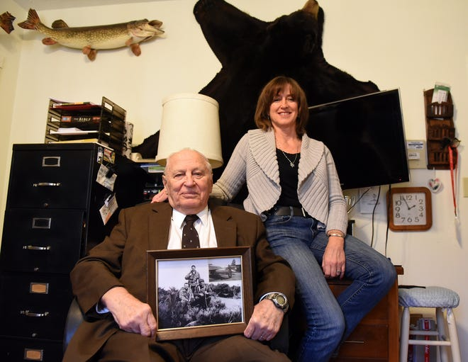 Furman Tinon with daughter, Diana Tinon Hall, in his Heath office with a service photo from an Army patrol in Korea. Tinon, aged 88, is thought to be the oldest continuously working Realtor in Licking County, and possibly all central Ohio.