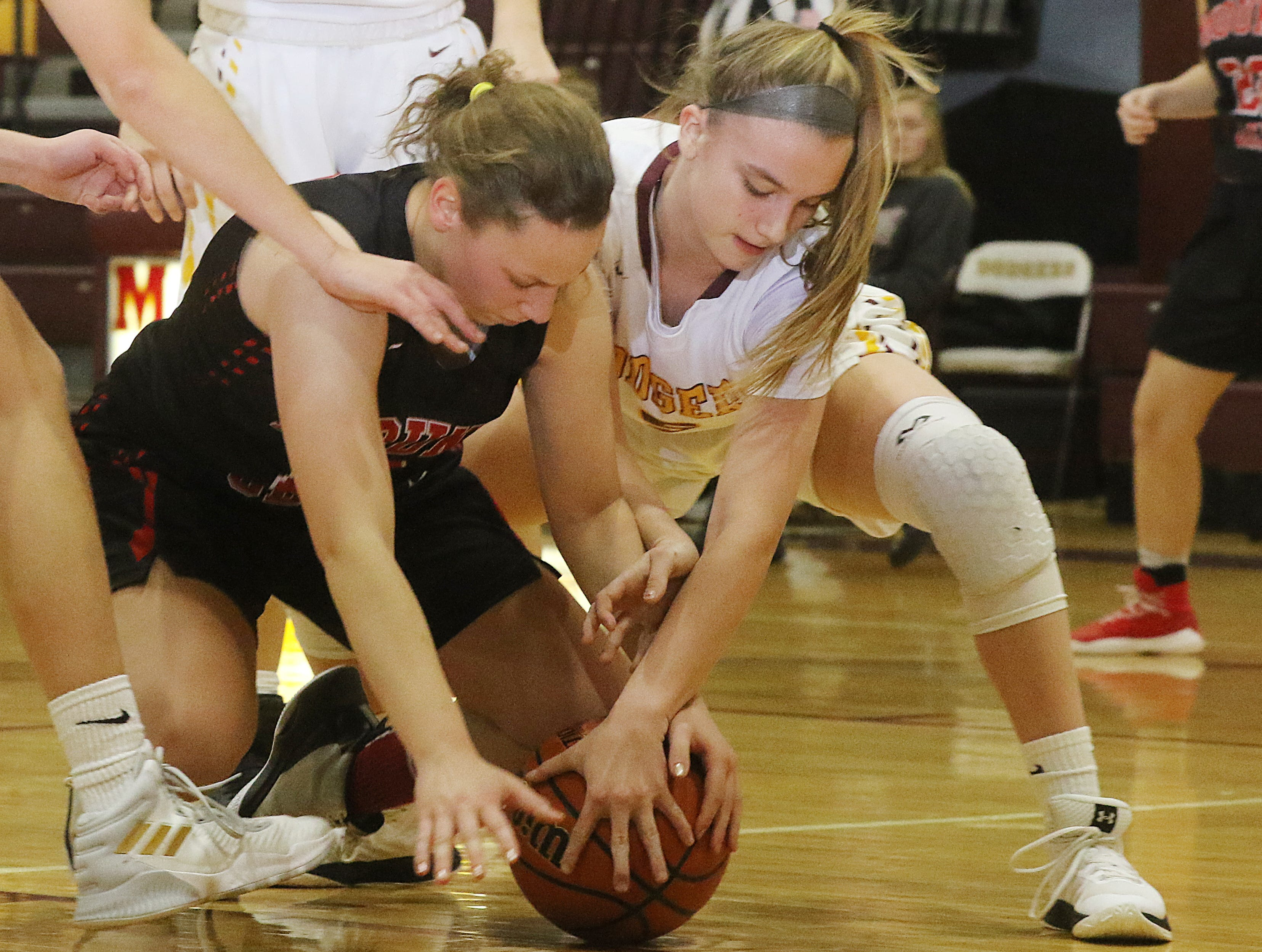 Gabby Grillo of Mount Olive fights for the ball with Julia Olesen of Madison in the second half.