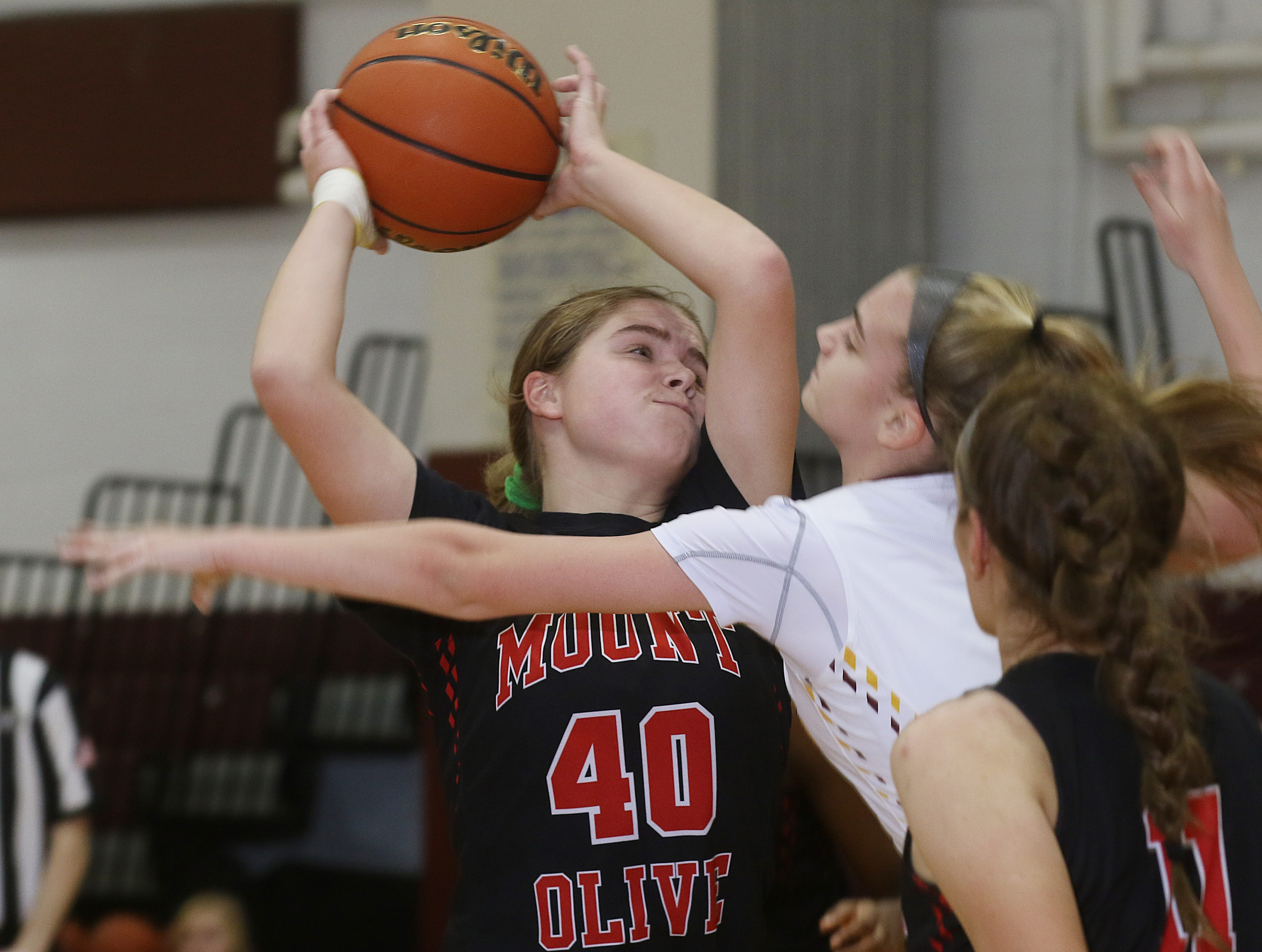 Ainsley Williams of Mount Olive tries to get the shot over Mikaela Timmermans of Madison in the first half.