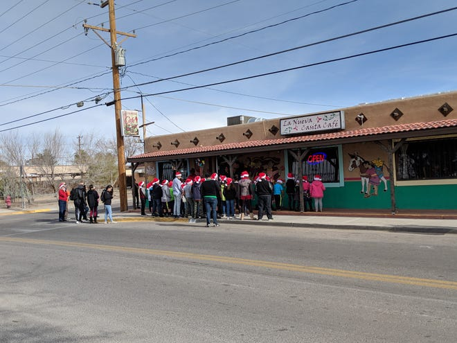 Children with the Weed and Seed program sing carols for the owners of La Nueva Casita Café to thank them for help with an enchilada fundraiser.