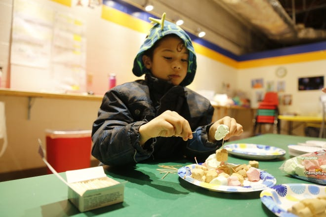 Zahir Hirahara assembles a Christmas tree using toothpicks and marshmallows during a science program Thursday at the E3 Children's Museum & Science Center in Farmington.