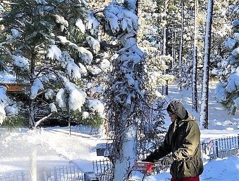 Homeowner clears a path out Thursday.