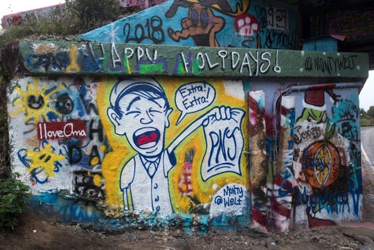 Street artist Monty Welt tags the Graffiti Bridge in Pensacola with his art Thursday, Dec. 27, 2018.