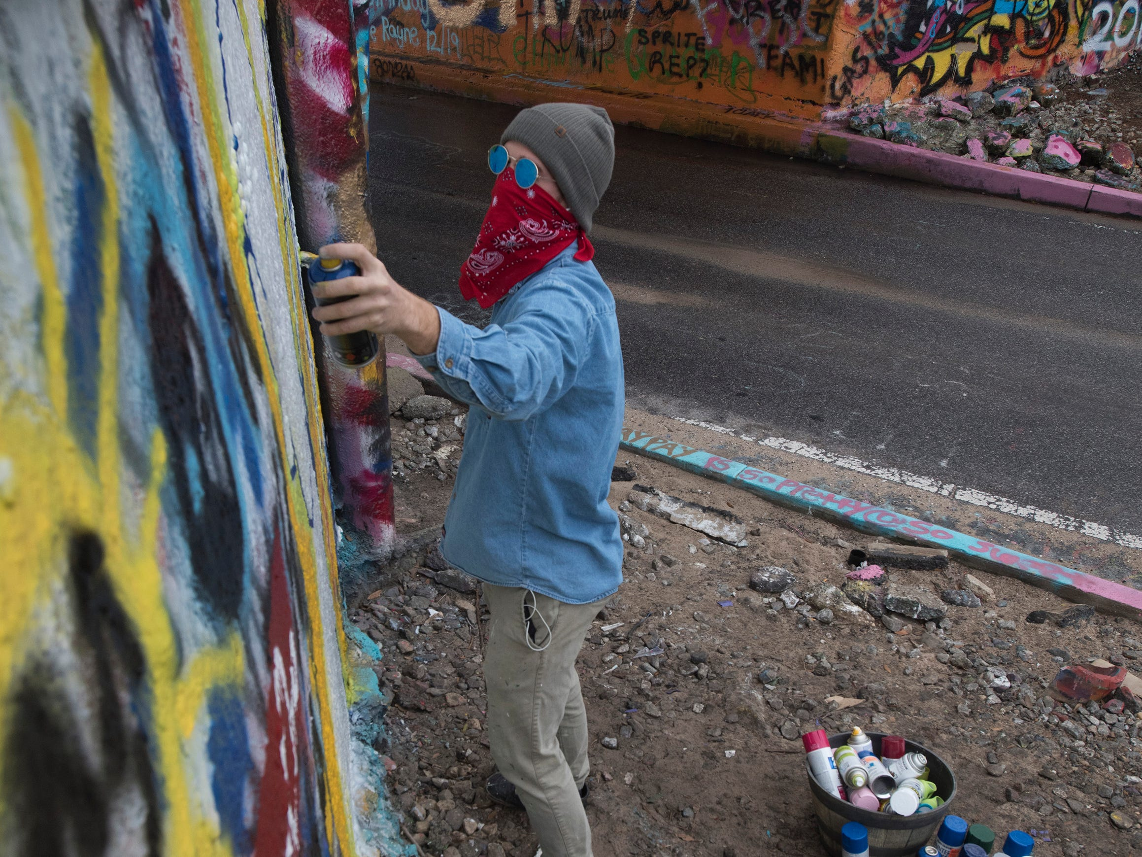 Street artist Monty Welt tags the Graffiti Bridge in Pensacola with his art Thursday, Dec. 27, 2018.