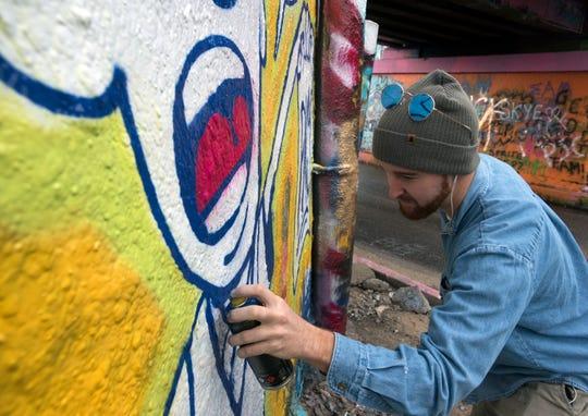 Monty Welt tags the Graffiti Bridge in Pensacola with his art Dec. 27, 2018.