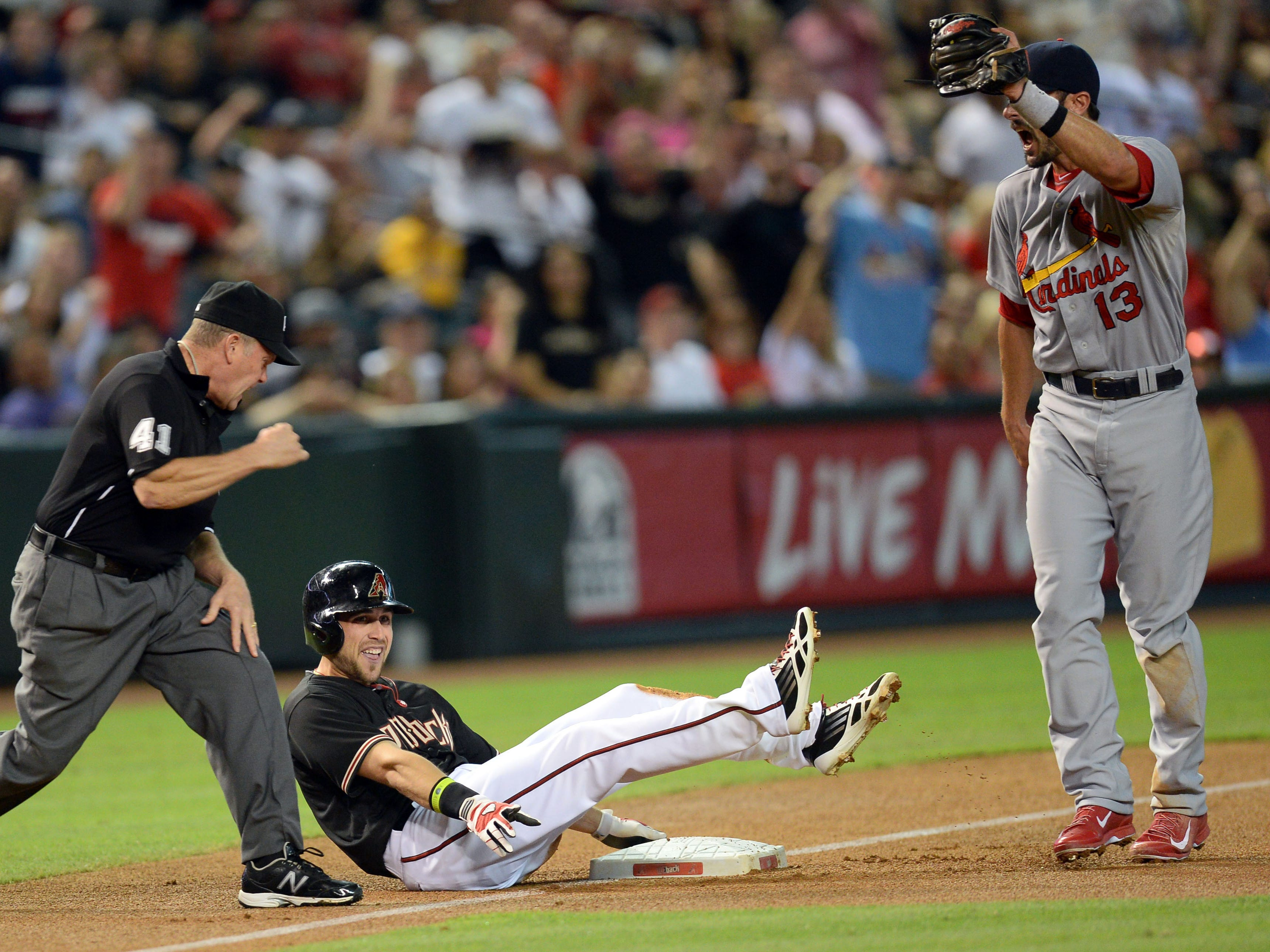 Sep 27, 2014; Phoenix, AZ, USA; Arizona Diamondbacks center fielder Ender Inciarte (5) is called out by third base umpire Jerry Meals (41) after being tagged out by St. Louis Cardinals third baseman Matt Carpenter (13) in the first inning at Chase Field. Mandatory Credit: Joe Camporeale-USA TODAY Sports